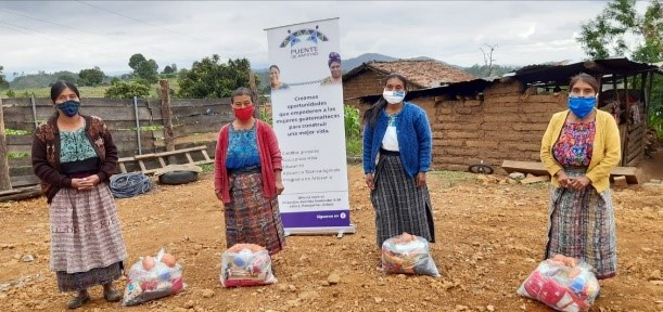 four women in masks with bags of food