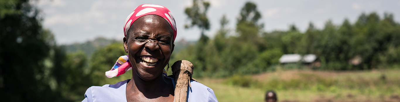 African women wearing a red head scarf smiling widely in front of a field