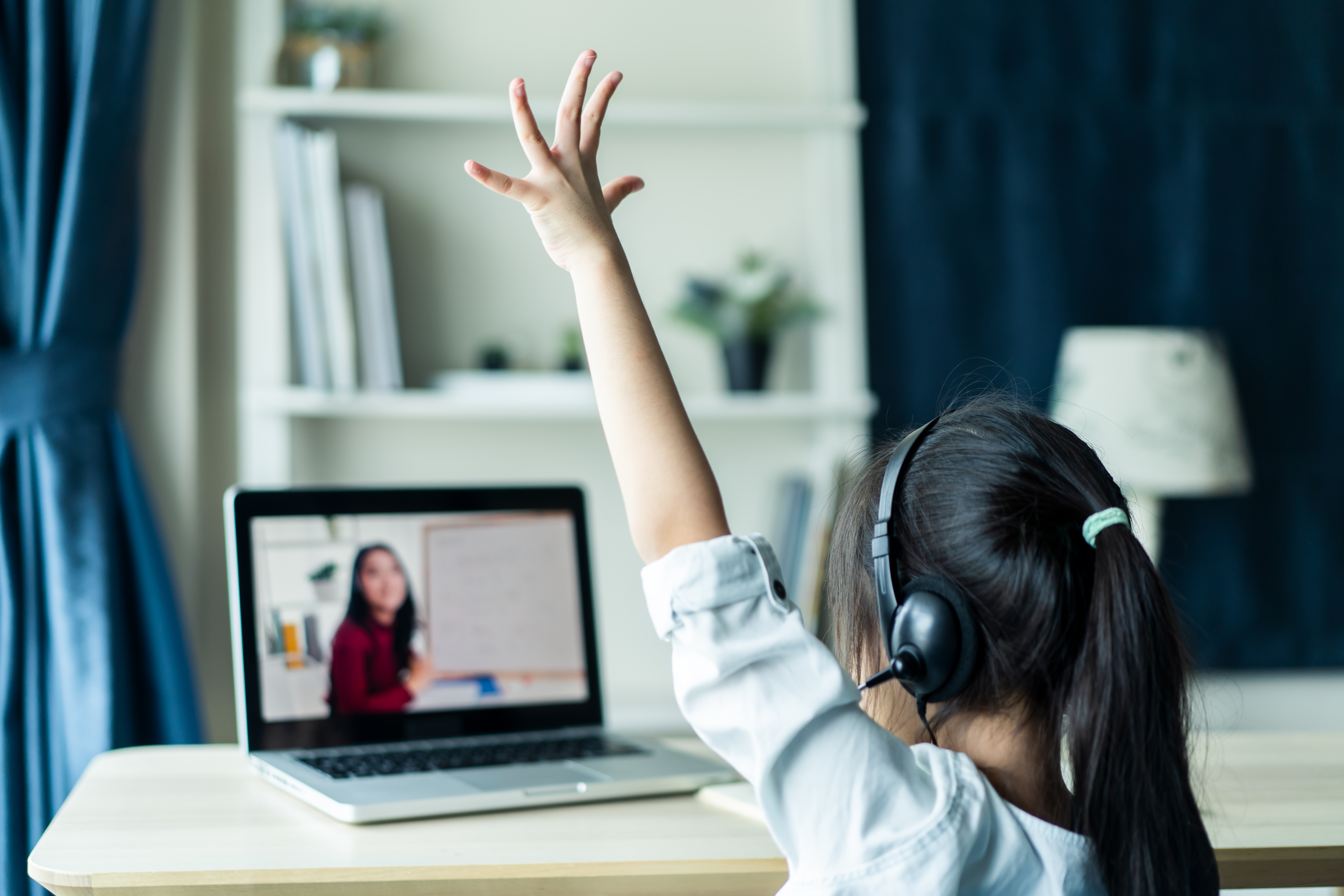 young female student raising hand during online class